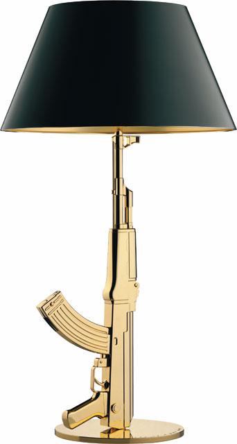 Lampada da tavolo Lounge Gun, della collezione Guns, dotata di supporto in alluminio pressofuso, con finitura dorata e paralume in carta plastificata nera, con interno dorato. Design Philippe Starck, produzione Flos.